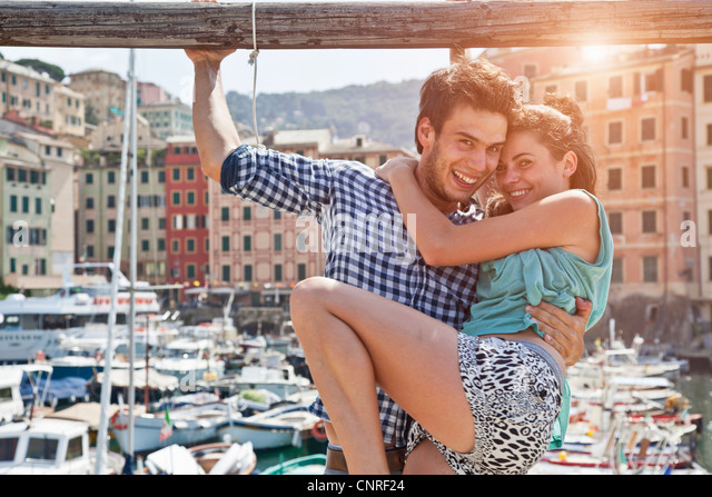 Couple hugging by urban pier - Stock Image