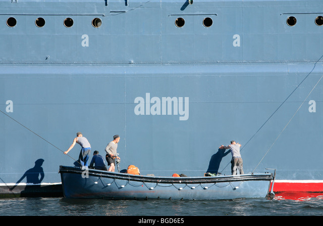 3 Russian sailors painting the Corvette Steregushchy during a naval parade in Saint Petersburg, Russia - Stock Image