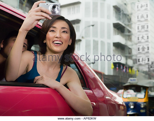Woman taking pictures from taxi - Stock Image