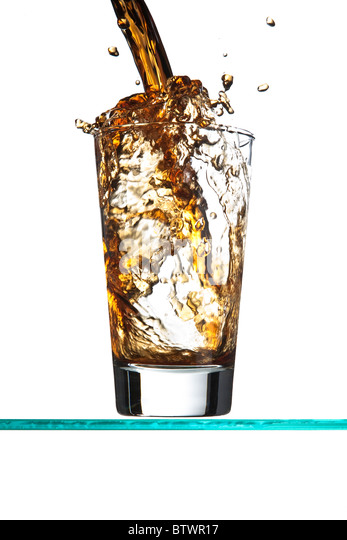 Pouring asoft drink, the liquid overflowing and spilling onto the table, on white. - Stock Image