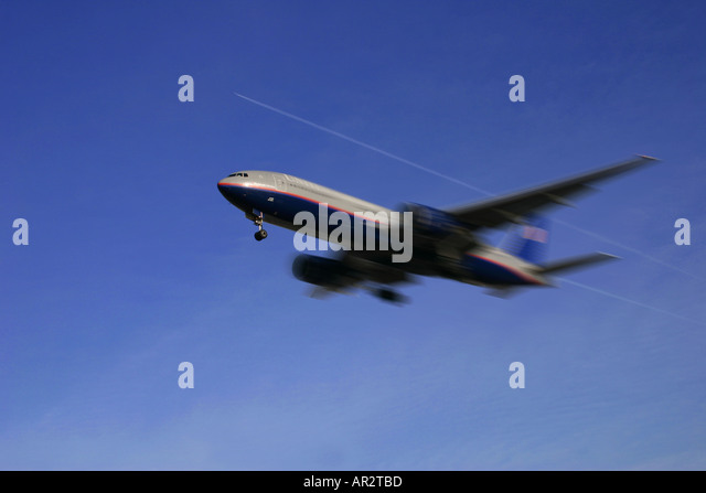 Airplane in flight on approach with another airliner above passing at high altitude - Stock Image