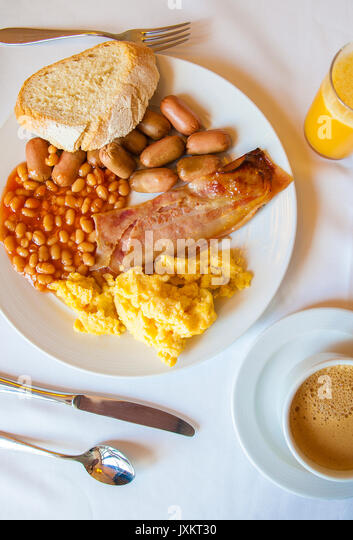 Nutritious english breakfast on a plate with bread, orange juice and and coffee cup - Stock Image