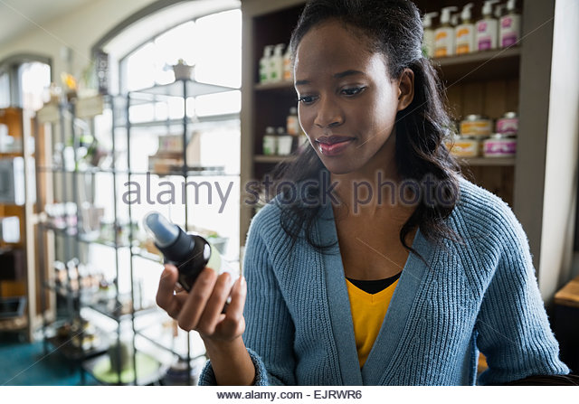 Woman examining bottle label in apothecary shop - Stock Image