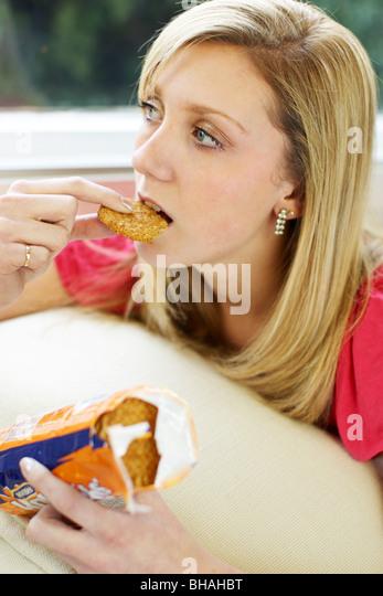 Teen girl eating biscuits - Stock-Bilder