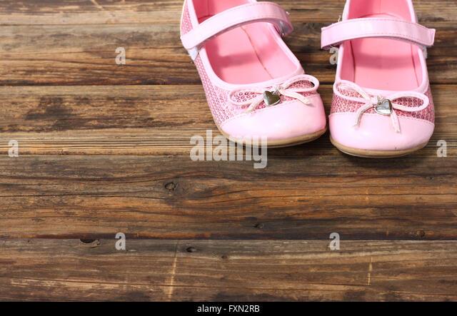 girl shoes over wooden deck floor. - Stock Image