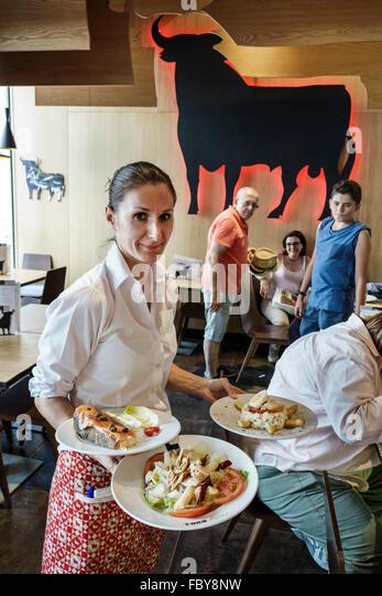 Madrid Spain Europe Spanish Hispanic Centro Plaza de Oriente Toro Tapas restaurant business plate serving waitress - Stock Image