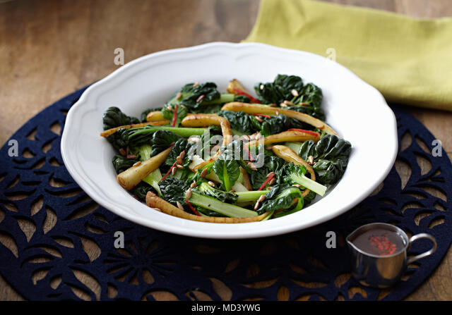 Chard and parsnip salad with pine nuts in bowl - Stock Image