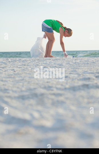 USA, Florida, St. Petersburg, Girl (10-11) cleaning beach - Stock Image