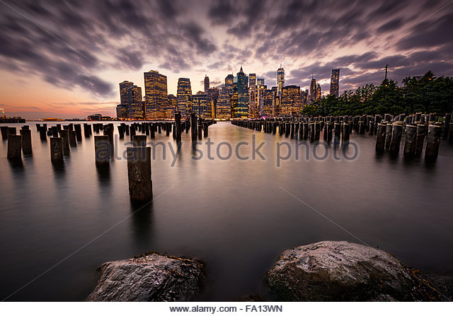 The Manhattan skyline with its skyscrapers and the wood pilings in the Hudson River during a dramatic and cloudy - Stock Image
