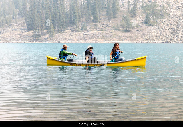 3 people paddling a canoe on Moraine Lake Banff National Park Alberta Canada - Stock Image