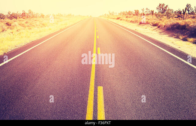 Vintage old film style endless country highway at sunset, travel adventure concept, Joshua Tree National Park, USA. - Stock-Bilder