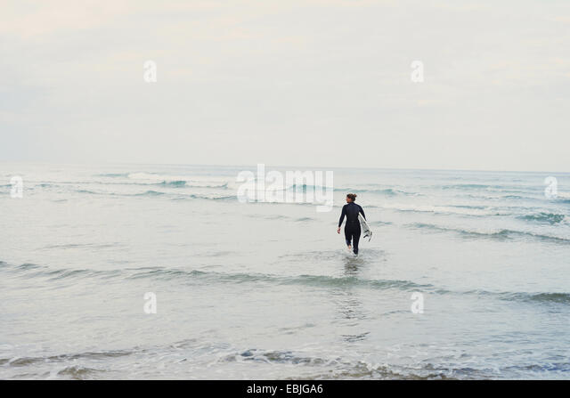 Surfer with surfboard walking into ocean, Lacanau, France - Stock Image