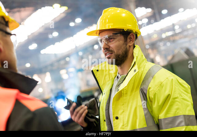 Steel workers talking in factory - Stock Image