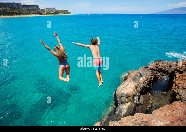 Summer fun, Friends cliff jumping into the ocean. - Stock Image