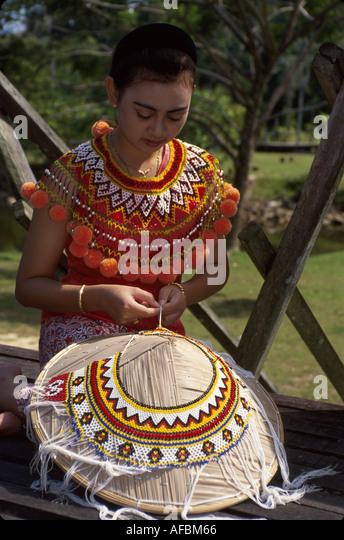 Malaysia Borneo Sarawak Kuching Cultural Village Iban tribe female ceremonial costume weaving hat - Stock Image