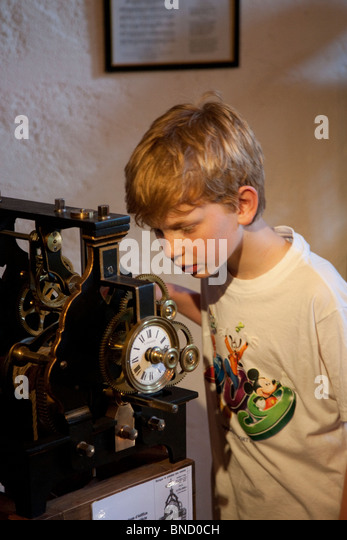 Boy looking at a clock mechanism in a museum in a French village. - Stock Image