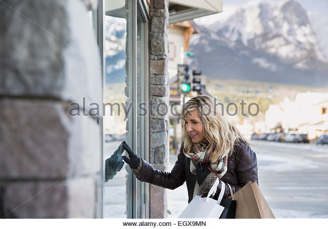 Woman window shopping at storefront - Stock Image