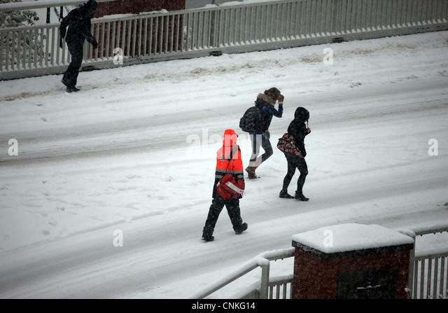 Royal Mail postman and young people walking on the road through a snow storm - Stock Image