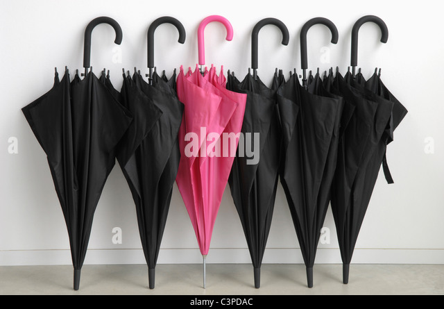 Black umbrellas with one pink umbrella - Stock Image