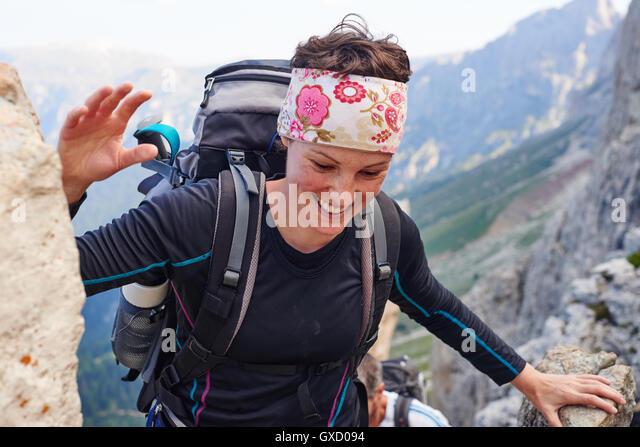 Woman hiking up mountain smiling, Austria - Stock Image