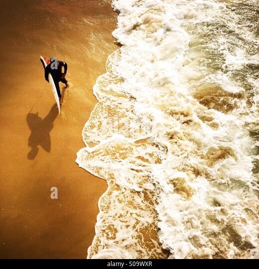A surfer waits at the shoreline to surf. Manhattan Beach, California USA. - Stock Image