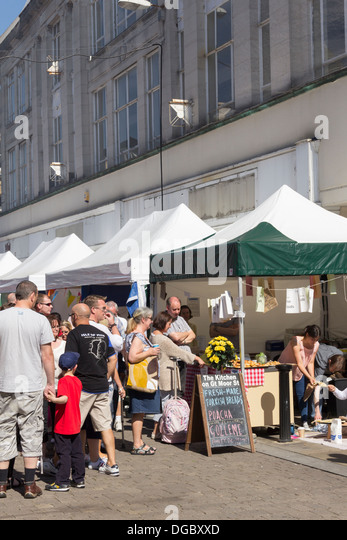 Visitors in Market Street crowd round 'The Kitchen on Great Moor Street' stall at the Bolton Food Festival - Stock Image