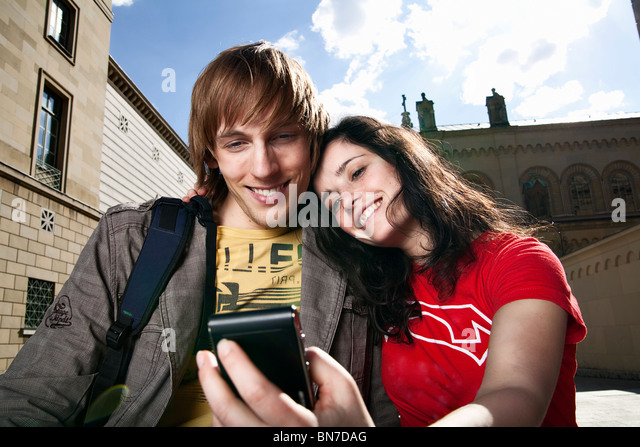 Young tourists looking at mobile phone - Stock Image