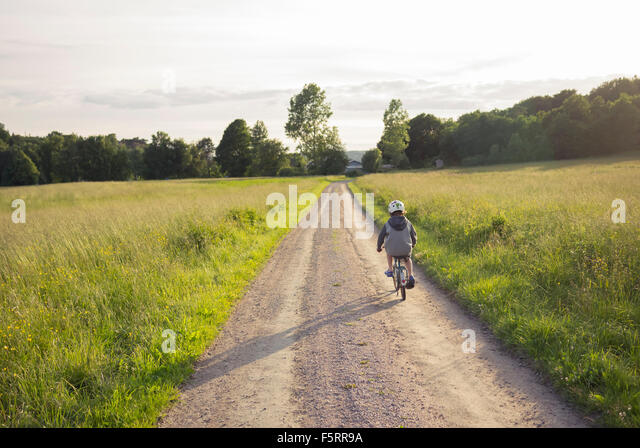 Sweden, Bohuslan, Halleback, Boy (10-11) cycling away along earth road leading through fields - Stock Image