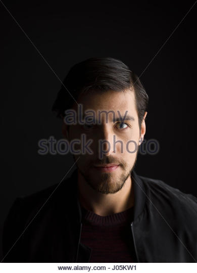 Portrait serious brunette man with beard against black background - Stock Image