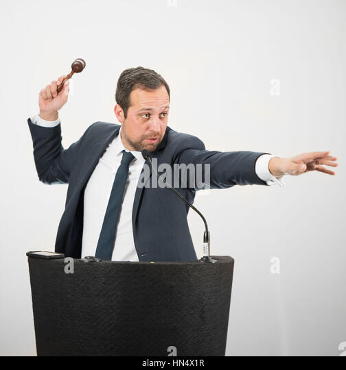 A male auctioneer in action holing a gavel during a live auction. - Stock Image