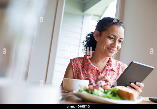 A young woman reading from the screen of a digital tablet, seated at a table. Coffee and a sandwich. - Stock Image
