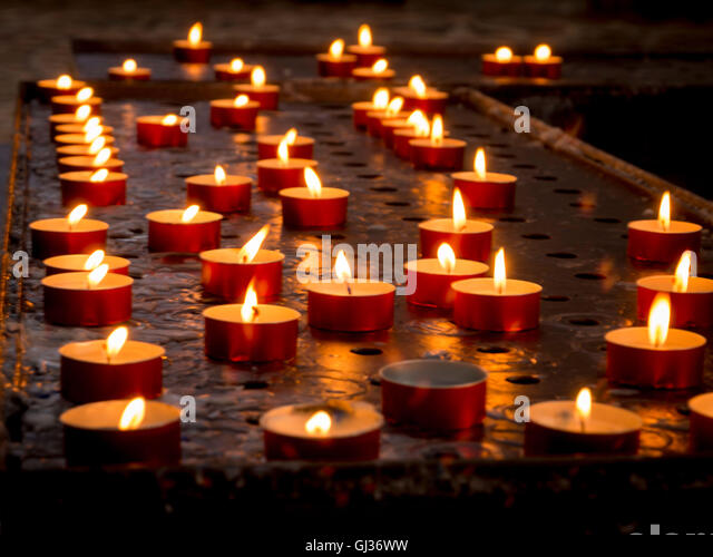 Prayer or Votive candles burning inside the church of Santa Maria della Salute, Venice, Italy. - Stock Image