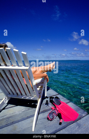 Woman relaxes on dock. - Stock Image
