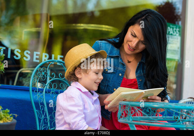 Young mother reading story book with son at sidewalk cafe - Stock-Bilder