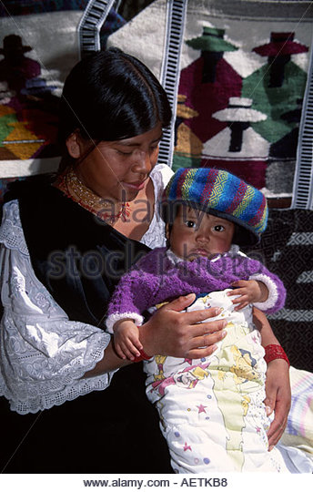 Ecuador Quito Alameda Parc park Sunday Open Market Otavalo female young mother baby blankets - Stock Image