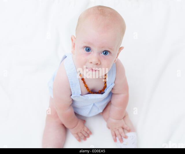 Baby girl (6-11 months) sitting on bed and looking at camera - Stock Image
