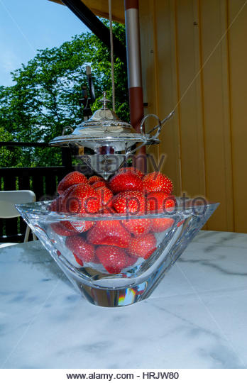 Big red and sweet strawberries in a glass bowl on a table on the verandah in summer. - Stock Image