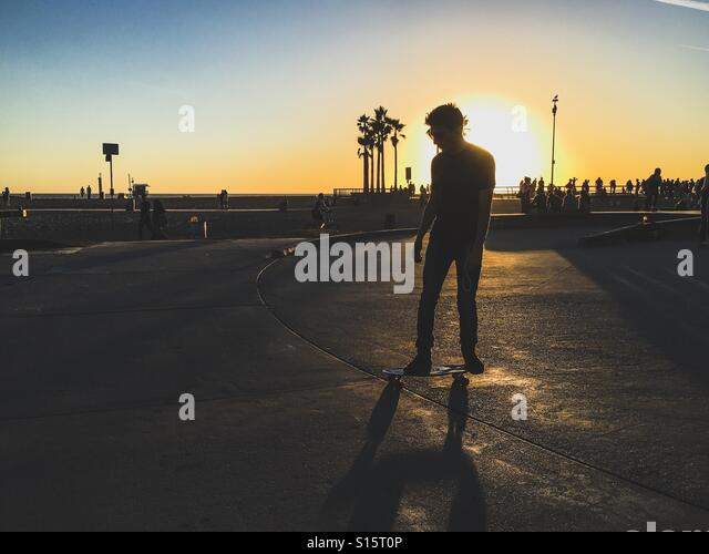 Man skating by the beach boardwalk - Stock-Bilder
