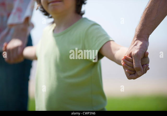 Boy holding hands with parents, cropped - Stock-Bilder