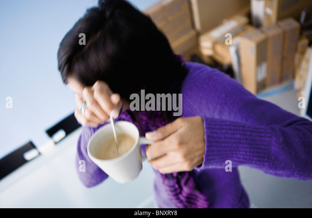 Woman turning away from camera, shyly covering face, coffee cup in hands - Stock Image