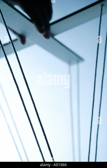 Hand on puppet strings - Stock-Bilder