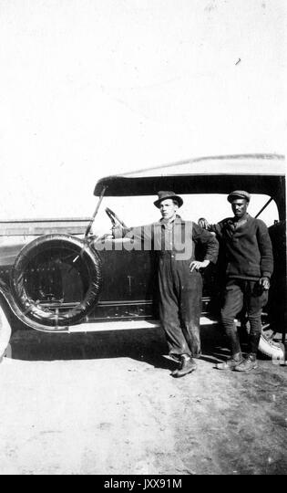 Full length portrait of two men standing by a car, one Caucasian man, one African American man, wearing uniforms, - Stock Image