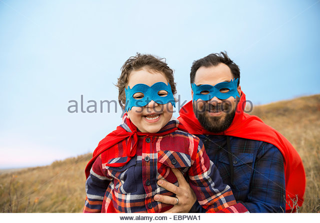 Portrait of father and son in superhero capes - Stock-Bilder