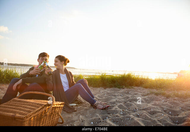 Young couple picnicing on Bournemouth beach, Dorset, UK - Stock Image