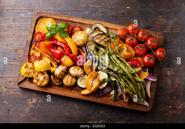 Grilled vegetables on cutting board on dark wooden background - Stock Image
