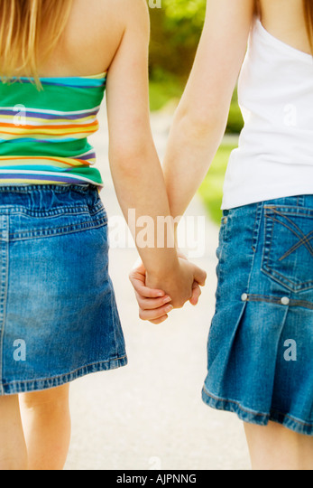 Rear view of girls holding hands - Stock Image