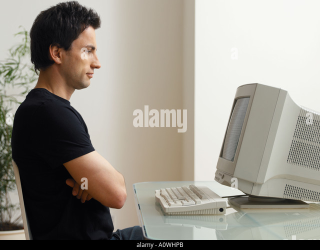 Man looking at computer screen - Stock Image