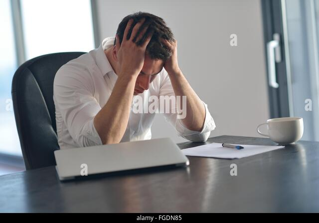 frustrated young business man working on laptop computer at home - Stock Image