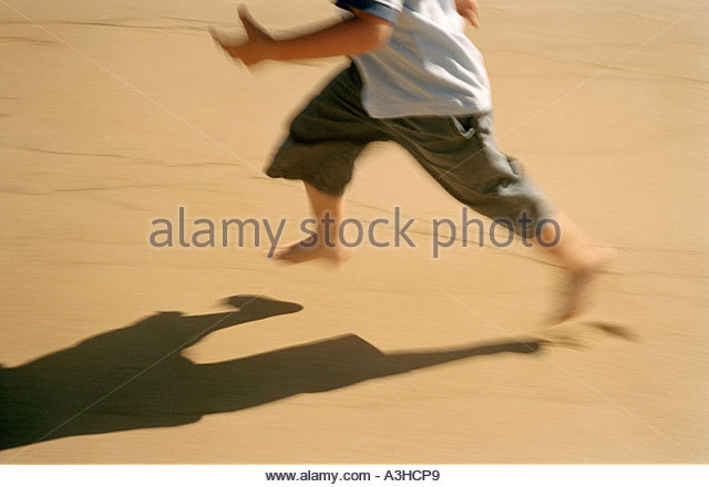 Child running down beach with shadow - Stock Image