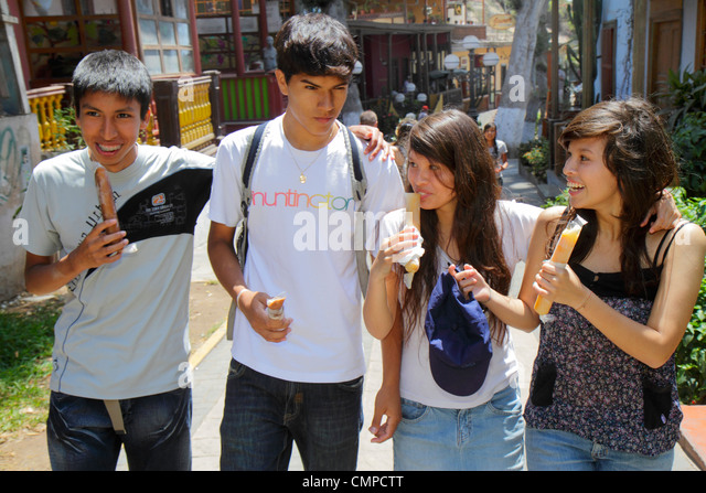 Lima Peru Barranco Bajada de los Banos Hispanic teen adolescent boy girl student snacking frozen snack socializing - Stock Image